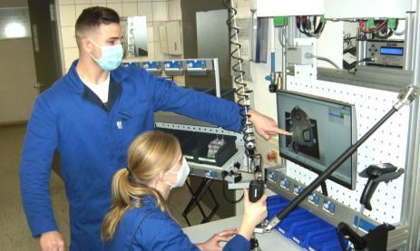 Die Schülerin Julia Schuster und ihr Kollege Nicolas Wolper, die im 3. Lehrjahr Feinwerkmechaniker sind, montieren eine Pumpe mit Hilfe einer interaktiven Anleitung am Montageplatz mittels ELAM.