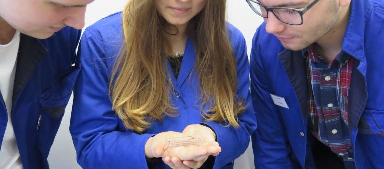 Feinmechanikerin Vanessa Baitinger hält eine Schale mit 500 Kleinst-Drehteilen in der Hand, links Björn Schlageter, rechts Christoph Wagner